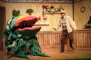 """Does it have to be Human? Does it have to be MINE?!"" ""Audrey II"" (voiced by Jaysen Robbins) orders Scott Leslie as ""Seymour Krelborn"" to ""Feed Me!"""