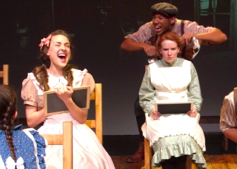 """Tho' one would be less troublesome, she wouldn't be half as fun--as Anne Of Green Gables!"" Xavier J. Watson as ""Gilbert Blythe"" shows-off to get ""Anne"" (Angela Griswold's) 'attention' while Emma Nossal as ""Josie Pye"" takes gleeful notice."