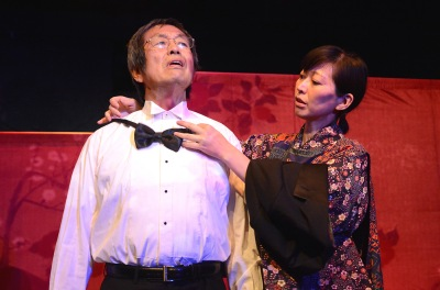 "Toshi Toda as an infamous public health official, ""Dr. Kazama"" gets ready for an address as Mika Santoh as ""Mrs. Kazama"" aids him"