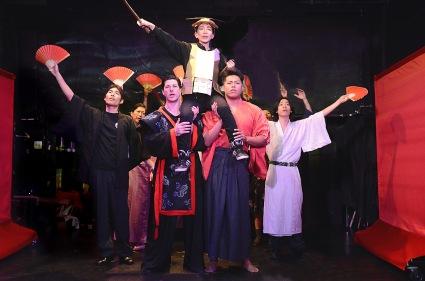 """Behold, the Child Warrior"": armor-clad Miko Santoh as the brave boy ""Koyo Ninomiya"" is held aloft by Takaaki Hirakawa, Michael Joseph, Ash Ashina, and Takuma Anzai for a triumphant march"