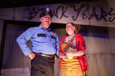 """Well, 'Little Sally', suffice it to say that in 'Urinetown, The Musical', everyone has to use public bathrooms in order to take care of their private business—that's the central conceit of the show…"" Ted Barton as ""Officer Lockstock"" tells Nicole Monet as ""Little Sally"" the way things are in the opening of ""The Coeurage Theatre Company's"" production of ""Urinetown: The Musical"""
